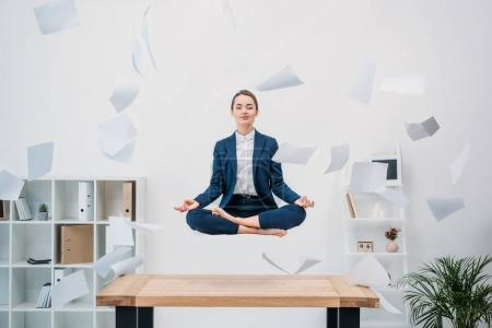 Photo for Smiling young businesswoman with closed eyes meditating while levitating at workplace with papers - Royalty Free Image