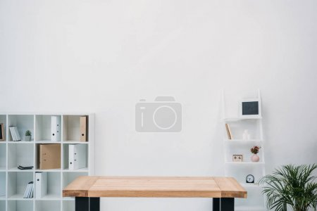 modern office interior with empty wooden table and folders on shelves