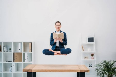smiling young businesswoman reading book while levitating at workplace