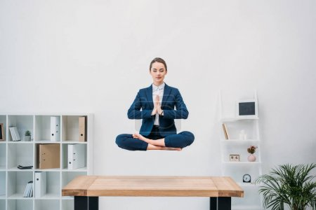 young businesswoman with closed eyes meditating while levitating at workplace