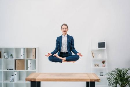 Photo for Smiling young businesswoman with closed eyes meditating while levitating at workplace - Royalty Free Image