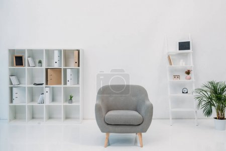 Photo for Modern office interior with grey armchair and folders on shelves - Royalty Free Image