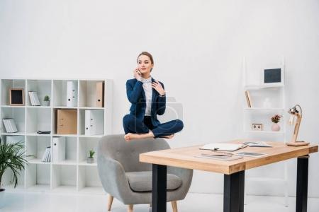 Photo pour Belle jeune femme d'affaires parler de smartphone en lévitation sur lieu de travail - image libre de droit