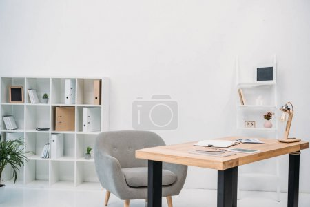 Photo for Modern office interior with papers and digital tablet on table - Royalty Free Image
