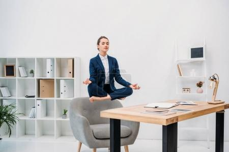 young businesswoman meditating with closed eyes while levitating at workplace
