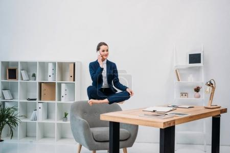 Photo pour Femme d'affaires, parler de smartphone en lévitation sur lieu de travail - image libre de droit