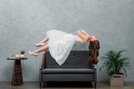 Photo pour Belle fille aux pieds nus, en vol stationnaire au-dessus de canapé - image libre de droit