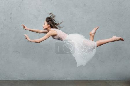Photo for Beautiful young woman in dress levitating and looking away on grey - Royalty Free Image
