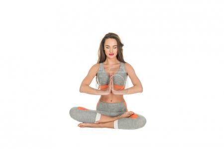 Photo for Young woman with closed eyes sitting in lotus position isolated on white - Royalty Free Image