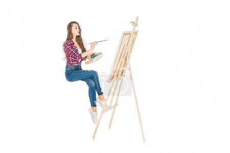 Photo pour Jeune femme en lévitation et la peinture sur chevalet isolé sur blanc - image libre de droit