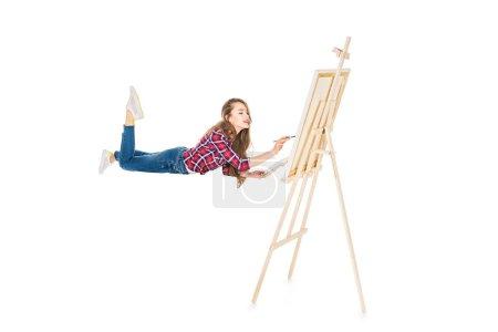 Photo pour Fille en lévitation et la peinture sur chevalet isolé sur blanc - image libre de droit
