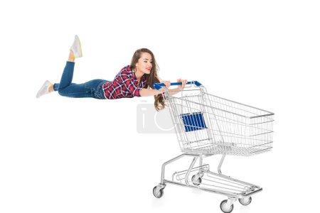 Photo pour Souriante jeune femme en lévitation avec caddie vide isolé sur blanc - image libre de droit