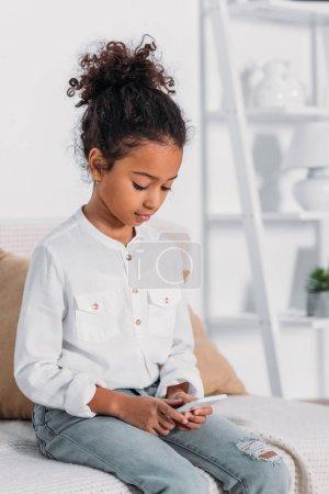 Photo pour Adorable enfant afro-américain utilisant un smartphone sur le canapé - image libre de droit