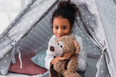 Photo pour Afro-américain enfant étreignant ours en peluche et regardant la caméra - image libre de droit