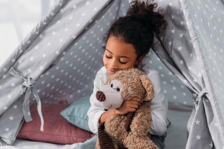 african american kid hugging teddy bear