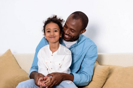 happy african american father and daughter on sofa at home