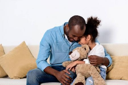 african american father hugging daughter with teddy bear