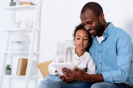 Photo for African american father and daughter watching something on tablet at home - Royalty Free Image