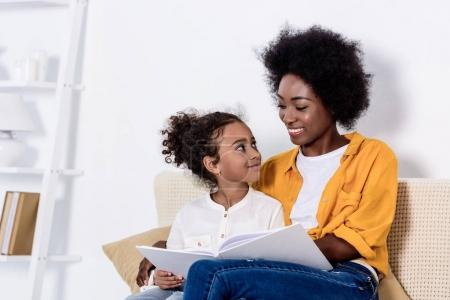 african american mother and daughter looking at each other on sofa at home