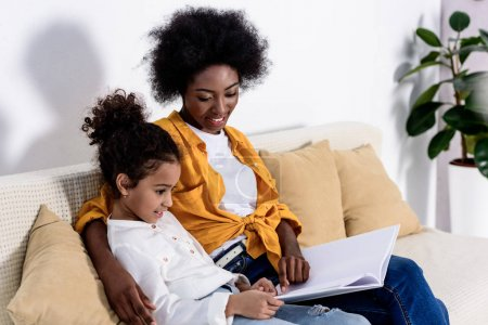 african american mother and daughter reading book on sofa at home