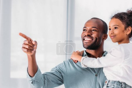 smiling african american father pointing on something to daughter