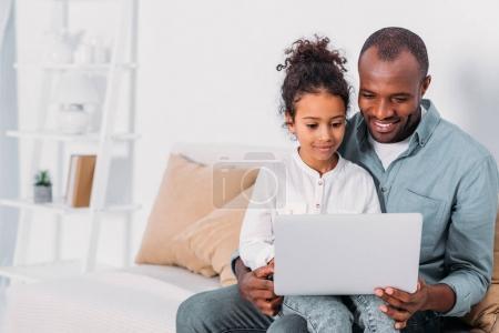 Photo pour Heureux père afro-américain et sa fille en utilisant un ordinateur portable à la maison - image libre de droit