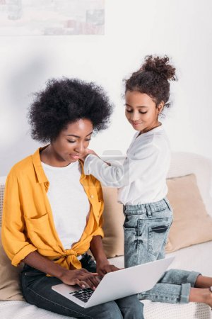 african american mother and daughter looking at laptop at home