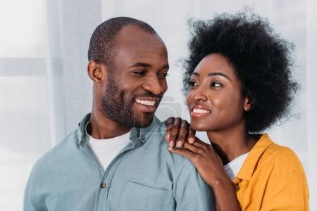 smiling african american couple hugging and looking at each other at home
