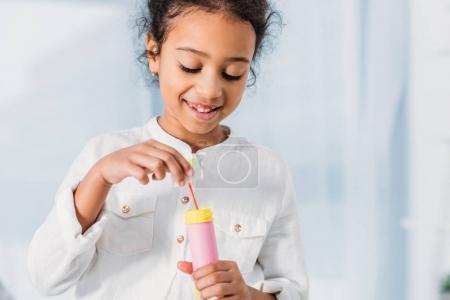 Foto de Sonriente niño afroamericano adorable haciendo pompas de jabón en casa - Imagen libre de derechos