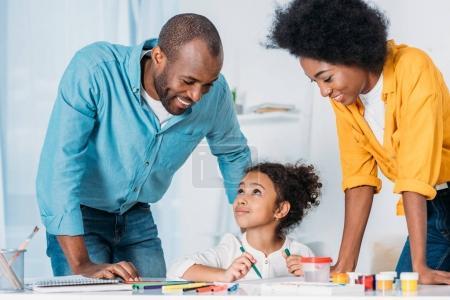 parents afro-américains en regardant les peintures de filles à la maison