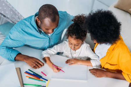 high angle view of african american parents looking at daughter paint at home