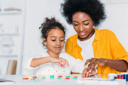 african american mother teaching daughter numbers at home