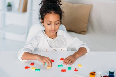 adorable african american kid learning colored numbers at home