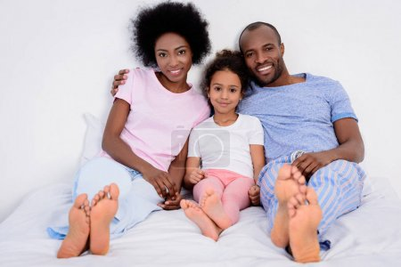 african american parents and daughter lying on bed and looking at camera at home