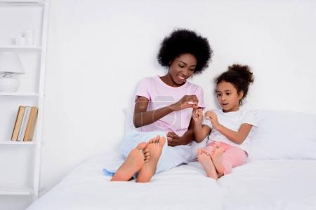 african american mother and daughter playing in bed at home