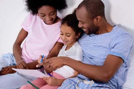Photo pour Parents afro-américains aider fille peinture dans l'album à la maison - image libre de droit