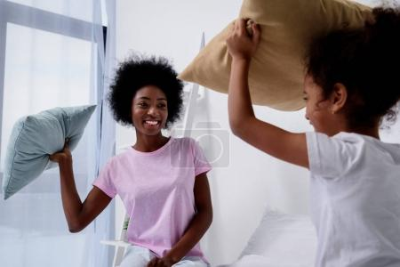 Photo for African american mother and daughter having fun with pillows at home - Royalty Free Image