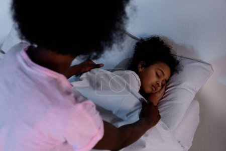 african american mother covering sleeping daughter with blanket at home