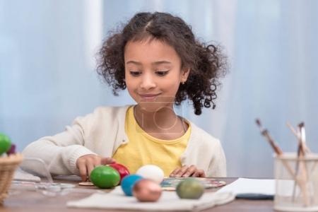 adorable african american kid playing with painted easter eggs