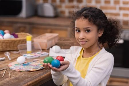 african american kid holding painted easter eggs in hands and looking at camera