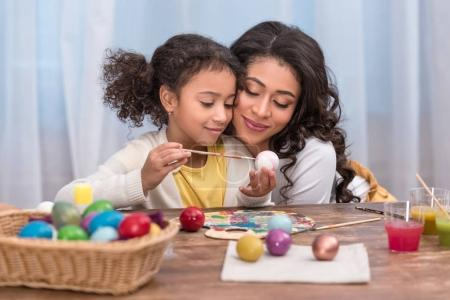 african american mother hugging daughter while she painting easter eggs