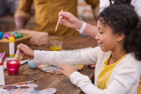 Photo for Cropped image of african american parents and daughter painting easter eggs - Royalty Free Image