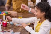 cropped image of african american parents and daughter painting easter eggs