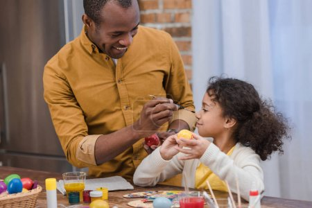african american father painting daughter nose while painting easter eggs