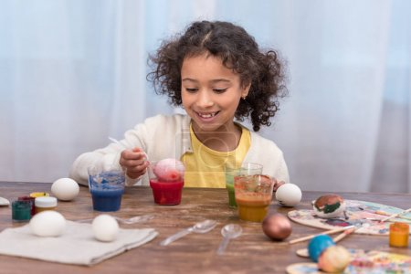 happy african american child painting easter eggs in glasses with paints