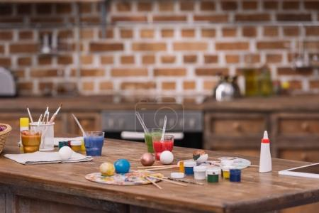 Photo for Painted eggs with paints and brushes on wooden table in kitchen, easter concept - Royalty Free Image