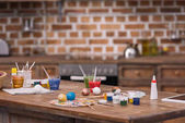 painted eggs with paints and brushes on wooden table in kitchen, easter concept