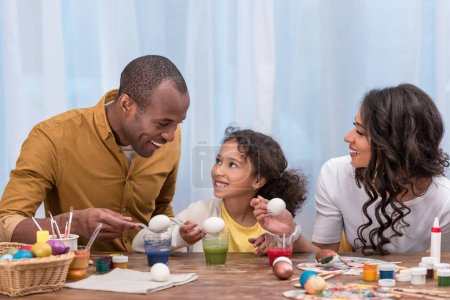 african american parents and daughter painting easter eggs and holding them above glasses with paints
