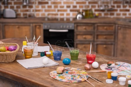 painted easter eggs with paints and brushes on wooden table