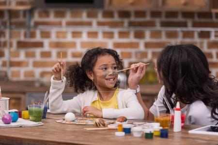 african american mother painting daughter face, easter concept